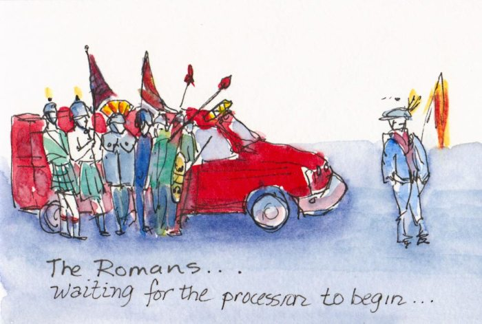Romans waiting by a small fire truck for a parade to begin