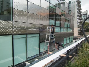 Window washers also have to squeegee the shiny stainless steel exterior of this building
